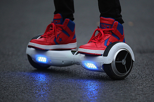 A youth poses as he rides a hoverboard. (Photo by Christopher Furlong/Getty Images)