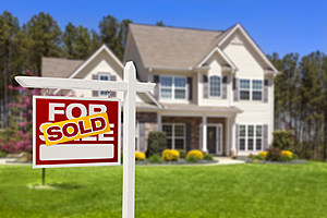 Sold Home For Sale Real Estate Sign and House (Andy Dean, ThinkStock)