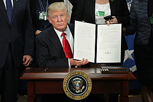 President Donald Trump (C) displays one of the two executive orders he signed during a visit to the Department of Homeland Security