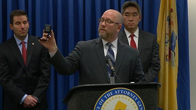 AG Chris Porrino holds micro-surveillance camera. Courtesy NJ Division of Consumer Affairs