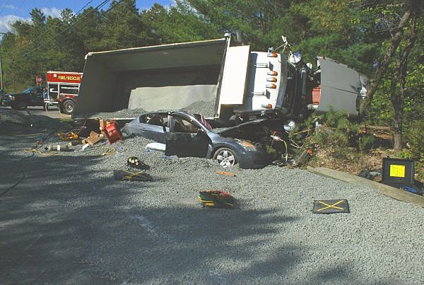 A car was crushed by a dump truck and its load Monday in Manchester. (Manchester Police)