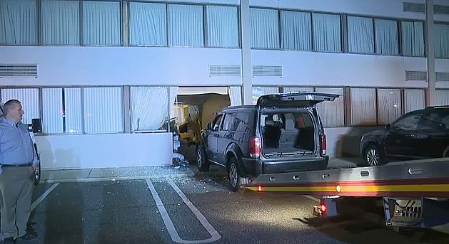 A SUV being towed out of a wall at the Days Inn of East Brunswick