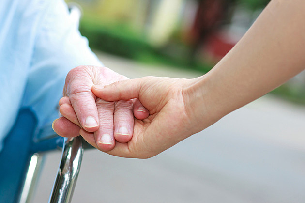 in wheelchair holding hands