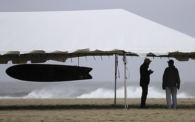 Men take shelter from the rain under a surfing school canopy as waves caused by Hurricane Jose crash on the beach in Belmar